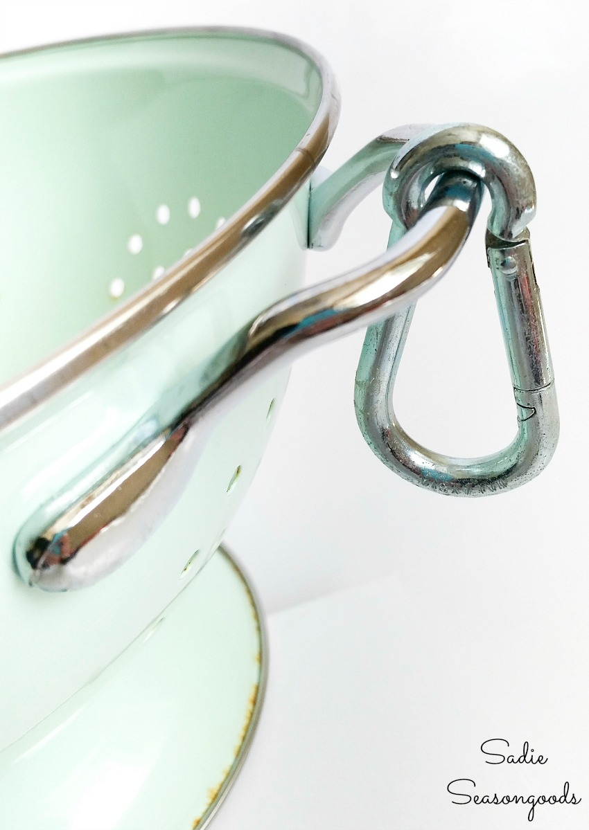 Carabiner on the handle of an enamel colander to attach the chain