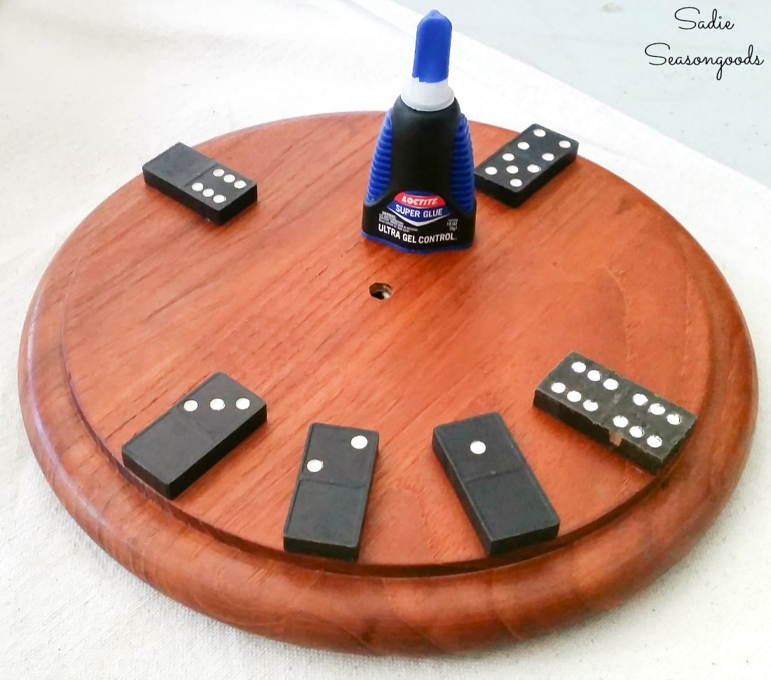 Gluing the vintage dominoes on a round cheese board