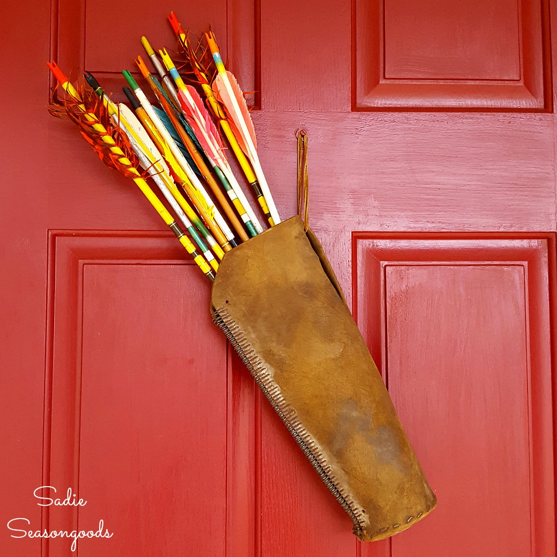 Vintage arrows or wooden arrows in a leather quiver as harvest decor and fall wreath for the front door