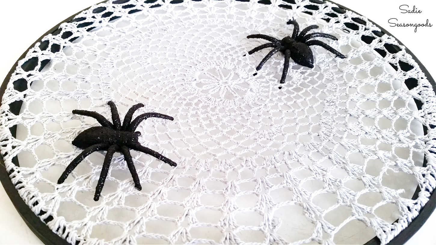 fake spiders on a spider web doily