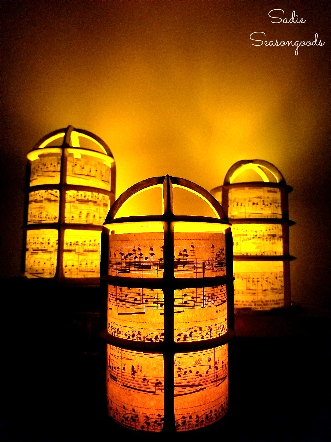 Christmas lantern or Christmas luminaries with a light bulb cage and old sheet music