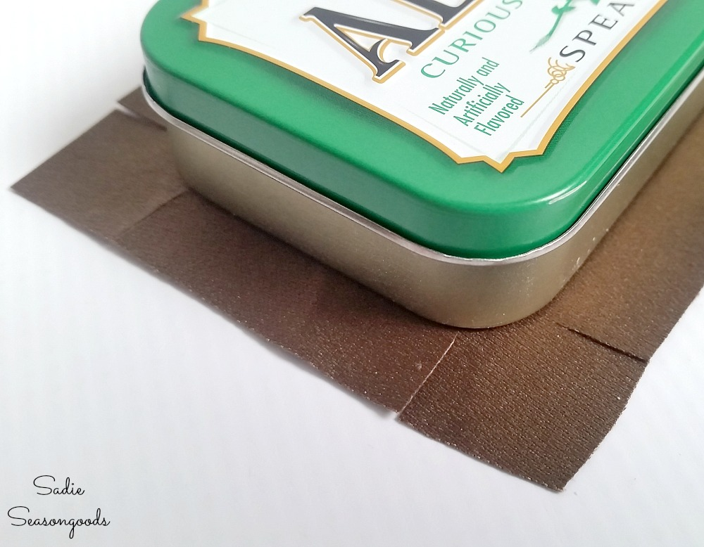 How to cover the corners of a mints tin with fabric by making perpendicular cuts to the Altoids tin