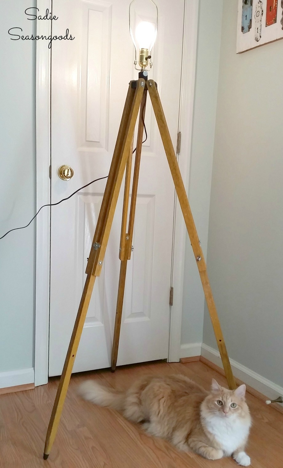 Industrial floor lamp made by wiring a lamp kit inside a surveyors tripod or wooden tripod by Sadie Seasongoods / www.sadieseasongoods.com