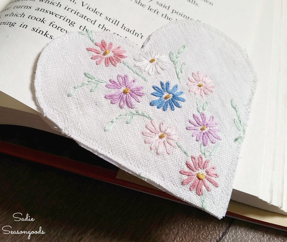Vintage tablecloths and embroidered linens that are damaged with holes and upcycled into a bookmarker