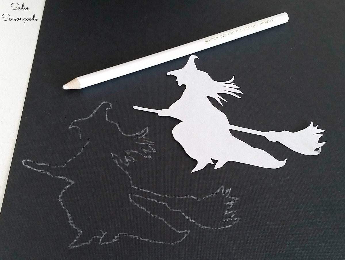 Tracing a flying witch on black cardstock paper