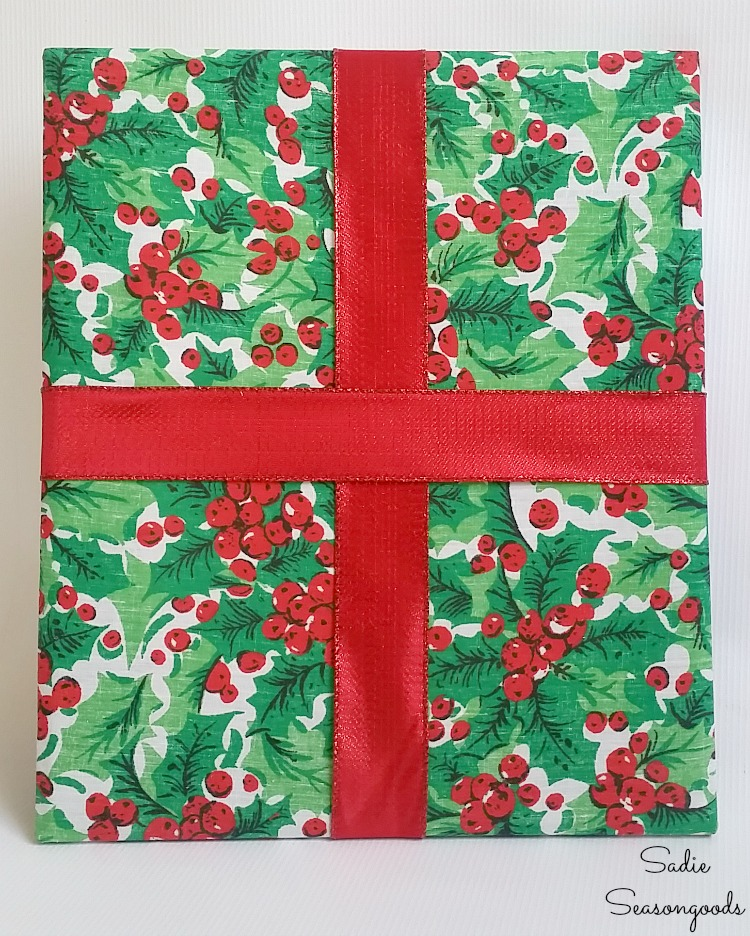 Adding the Christmas ribbon to decor that looks like wrapped presents with picture frames by Sadie Seasongoods