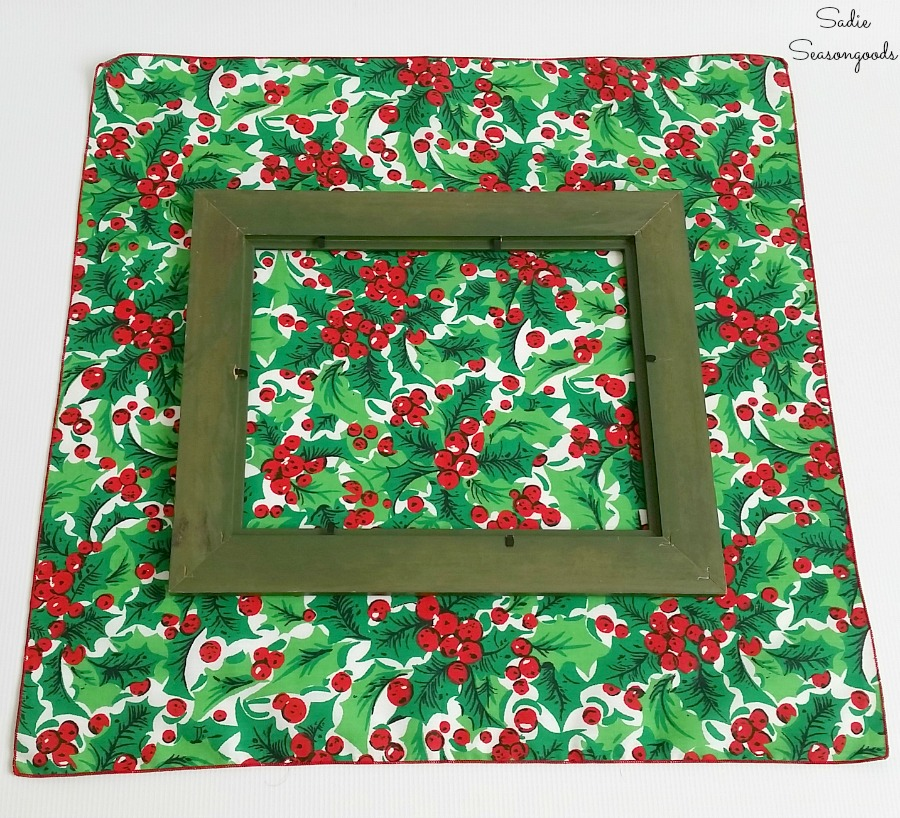 Laying a wooden frame on the Christmas fabric or Christmas napkins to make decor that looks like wrapped gifts by Sadie Seasongoods