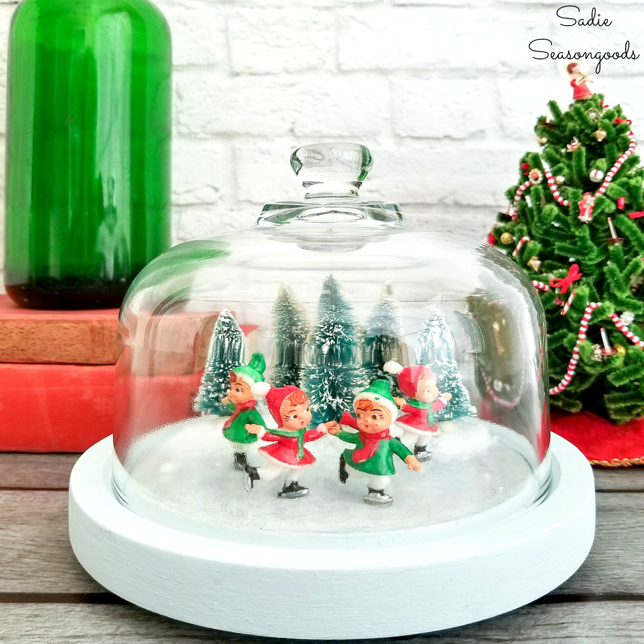 Making a winter scene with ice skaters on a frozen pond by upcycling a glass cloche or cheese dome