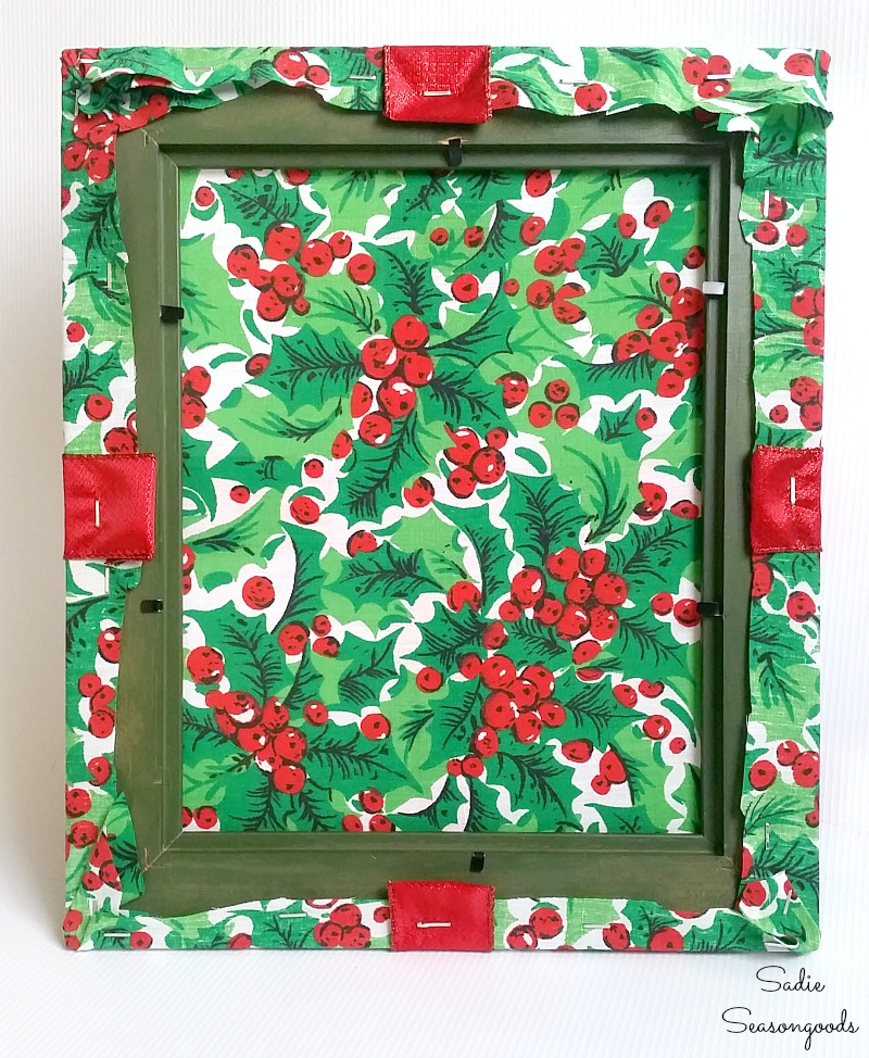 Using a staple gun to attach the Christmas ribbon into the back of a wooden photo frame by Sadie Seasongoods