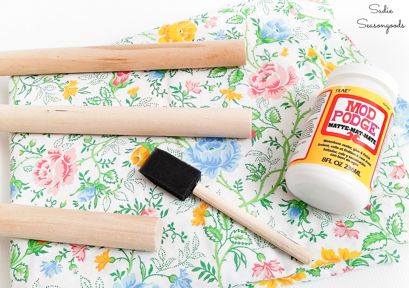 Decoupaging fabric onto wood with vintage sheets