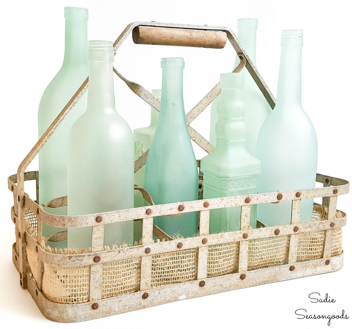 Sea glass bottles in a milk bottle basket as coastal decor