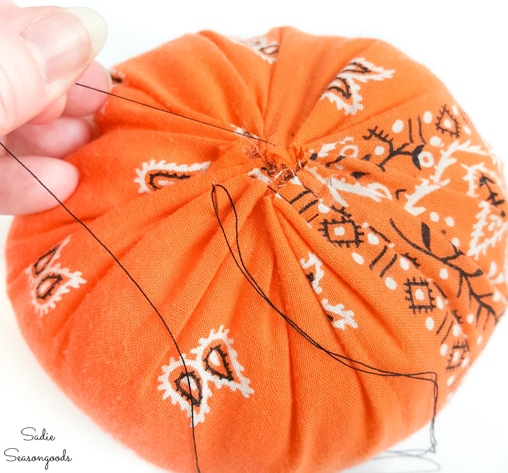 Sewing shut a fabric pumpkin from a Halloween bandana
