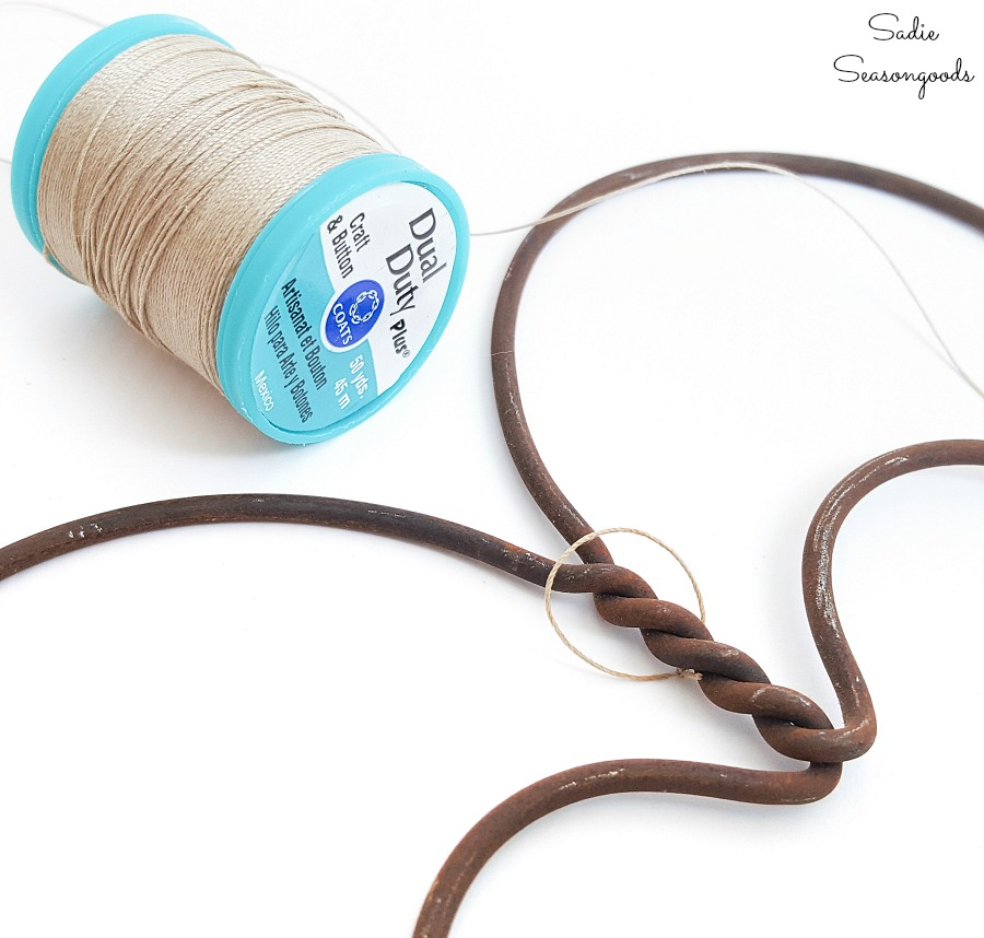 Tying a loop of craft thread to a rug beater to use as heart decorations for Valentines Day decor