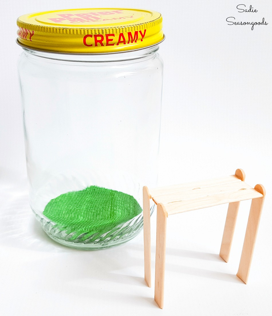 Popsicle sticks to build a potting bench to go in a peanut butter jar for Spring decor ideas