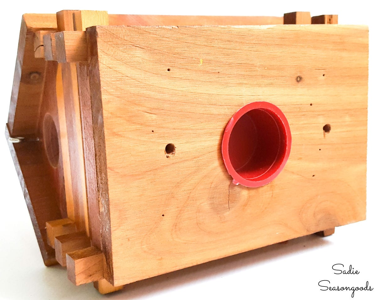 Drilling drainage holes in a log cabin birdhouse