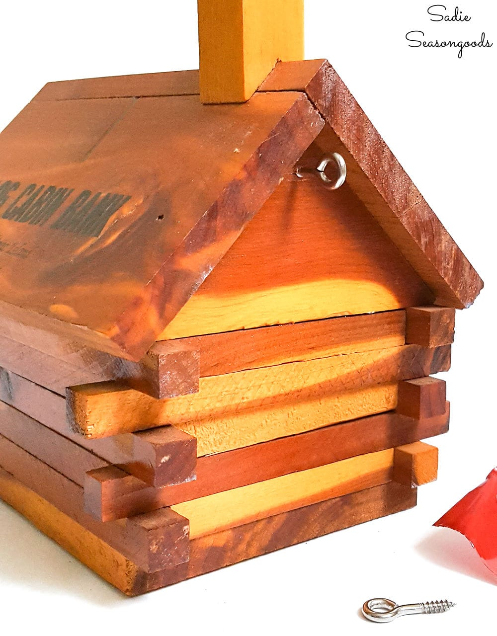 Hanging a log birdhouse from a vintage coin bank
