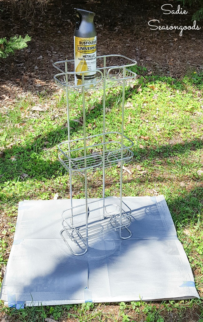 Spray painting metal of a shower basket for upcycling as a porch garden