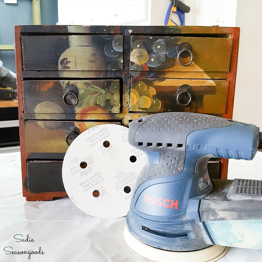 Bosch orbital sander to remove the paint from a small wooden chest