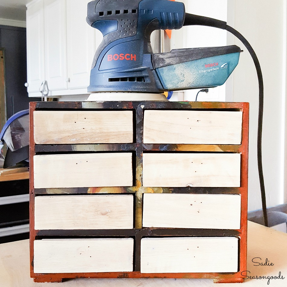 Refinishing a mini chest of drawers by sanding off the paint