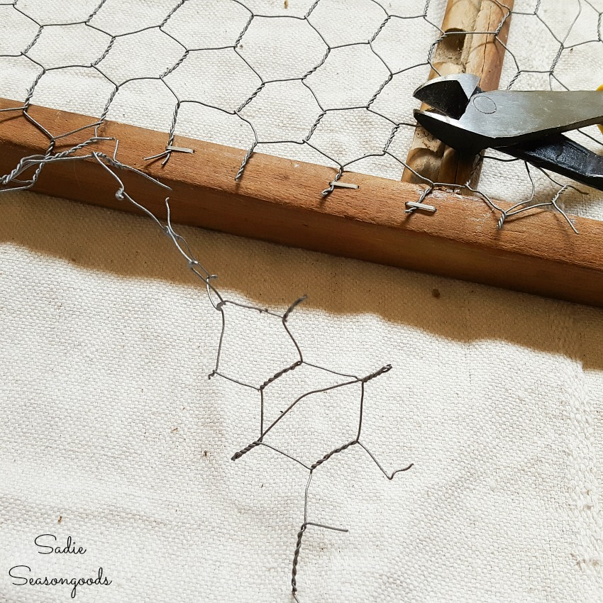 Trimming the chicken wire that was attached to the back of a vintage washboard