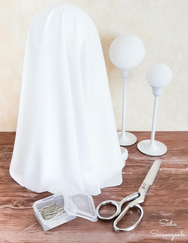 Halloween ghost decor with styrofoam balls and brass candlesticks
