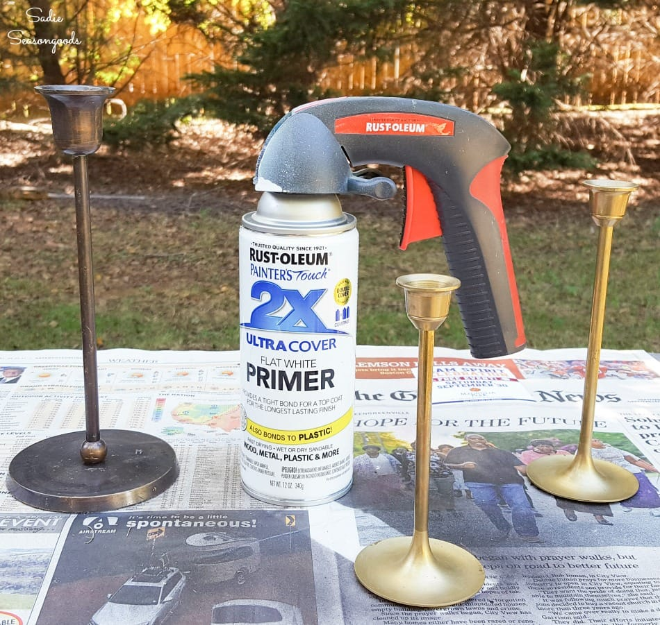 Spray painting the metal candlesticks with white primer