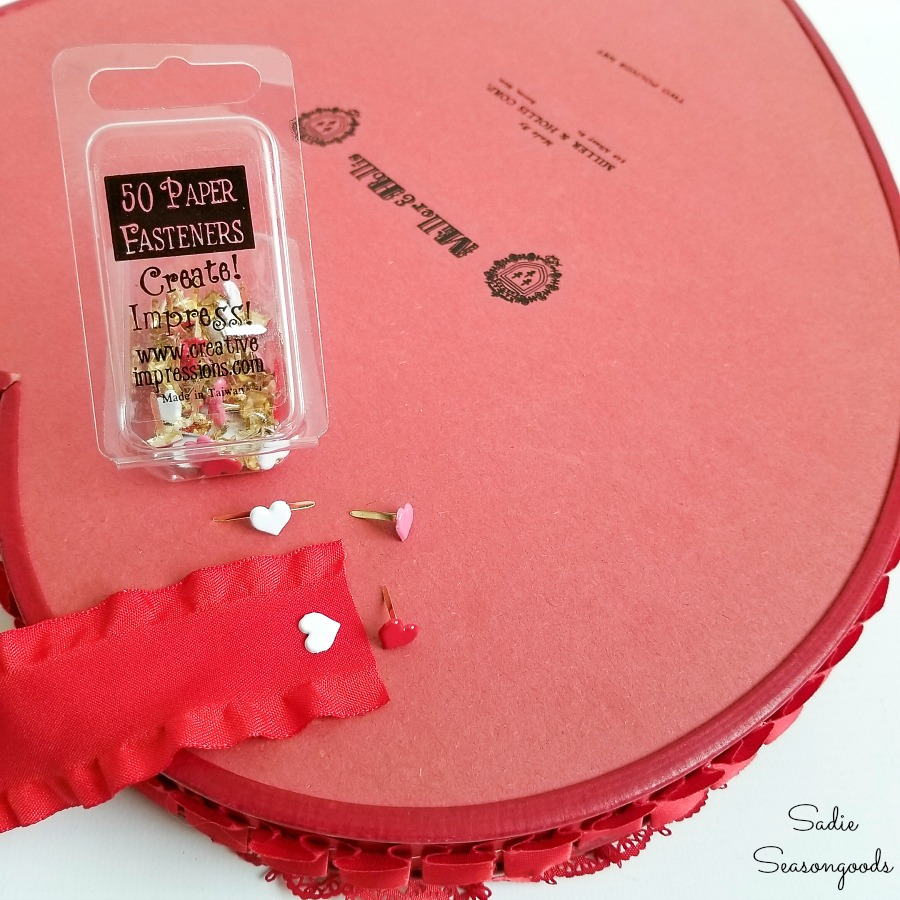 Attaching a hanging ribbon to the back of a chocolate heart box that will be Valentine's Day home decor
