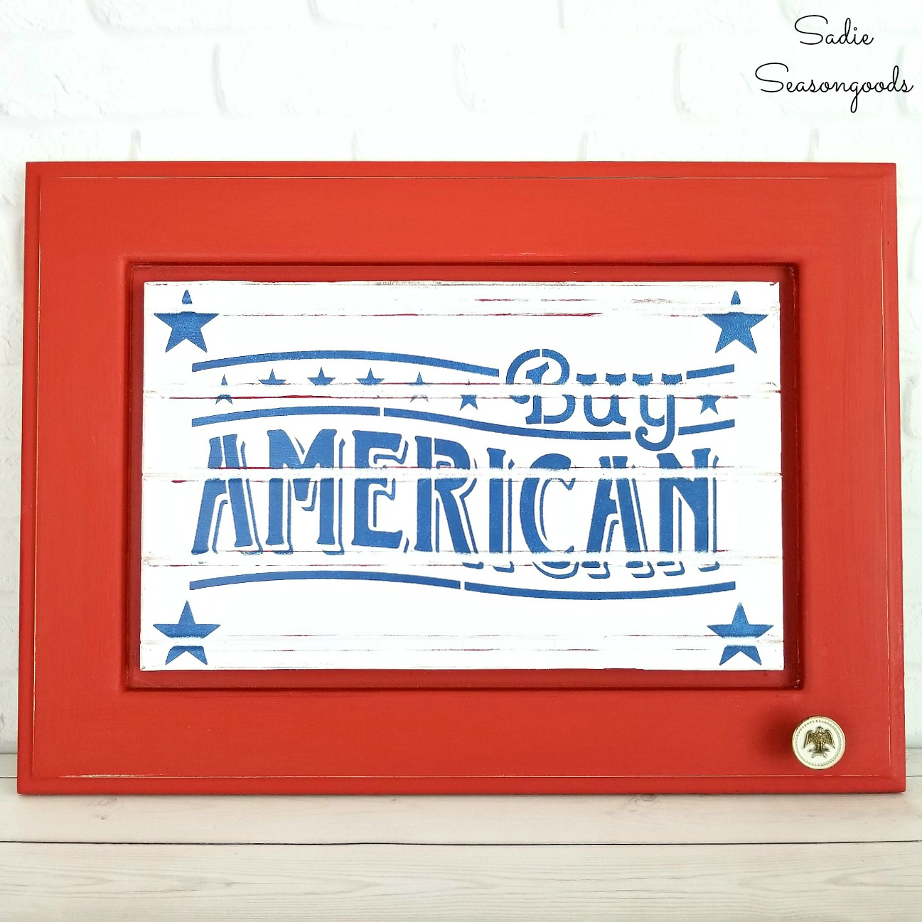 Patriotic decor that looks like the garage signs or vintage metal signs by upcycling a cabinet door with a patriotic slogan by Sadie Seasongoods