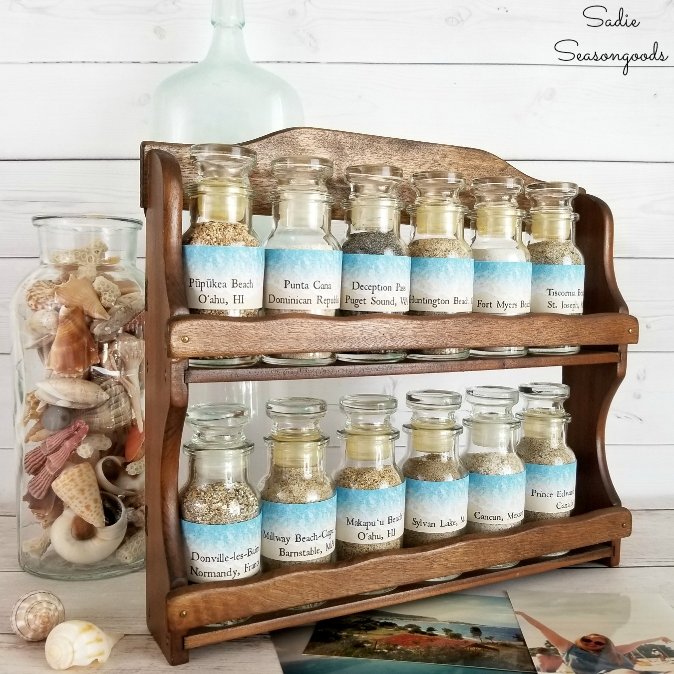 Upcycling a wooden spice rack to display a beach sand collection of beach souvenirs for coastal decor by Sadie Seasongoods