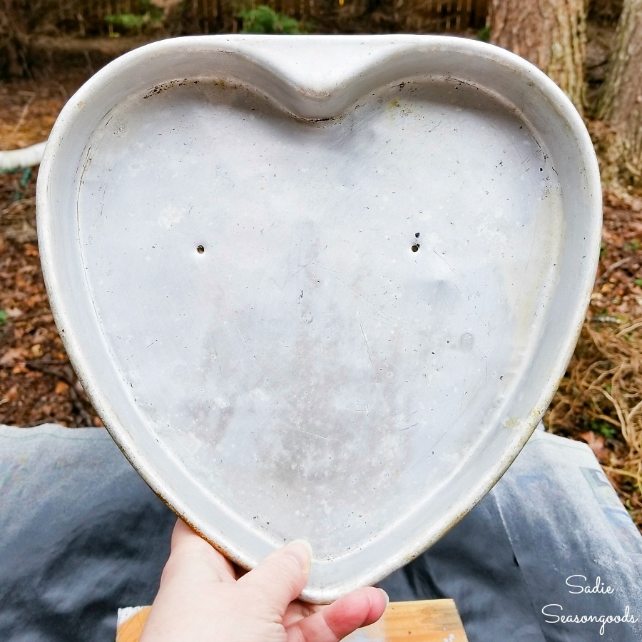 Drilling holes through the heart shape cake pans before upcycling into heart decorations