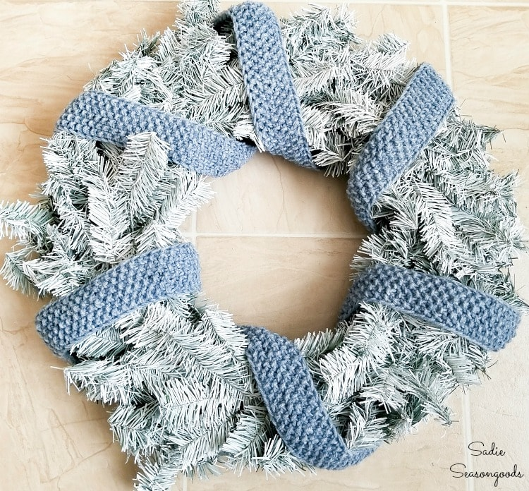 Knitted ribbon as a scarf on a DIY winter wreath