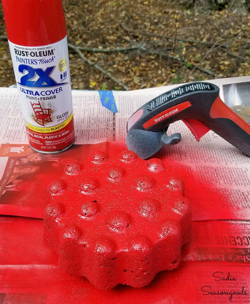 Spray painting the decorative garden stones or concrete lawn ornaments