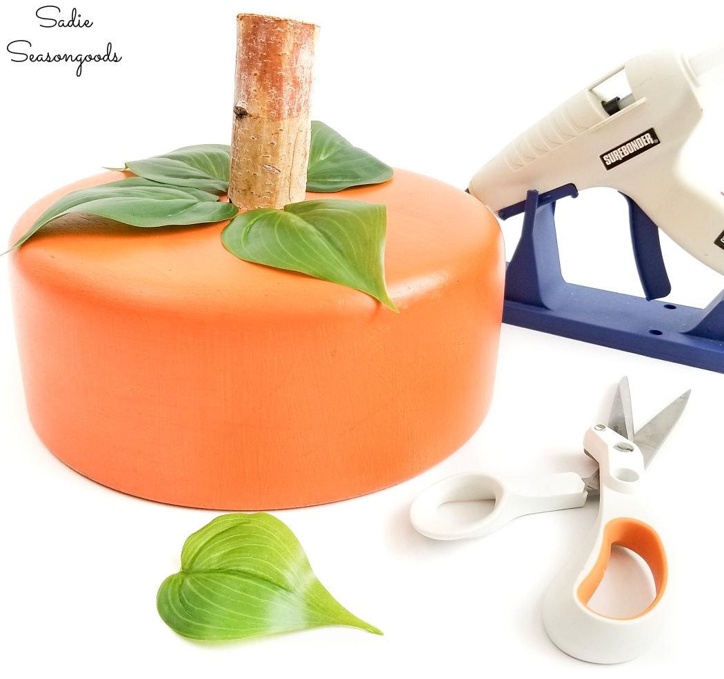 adding leaves to a pumpkin centerpiece