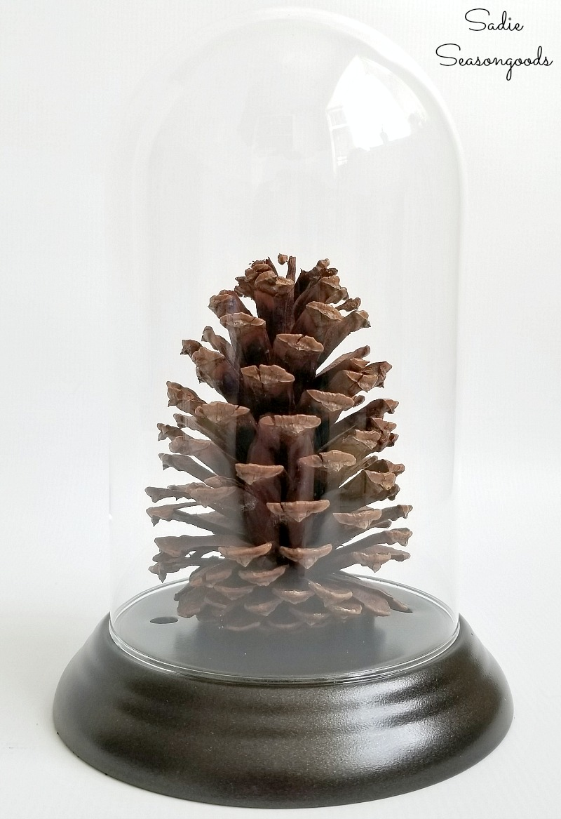 Glass cloche from a dome clock to display the log cabin decor for a winter cabin