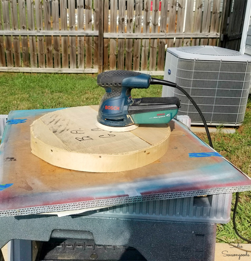 Sanding a wood cheese box to remove writing and marker