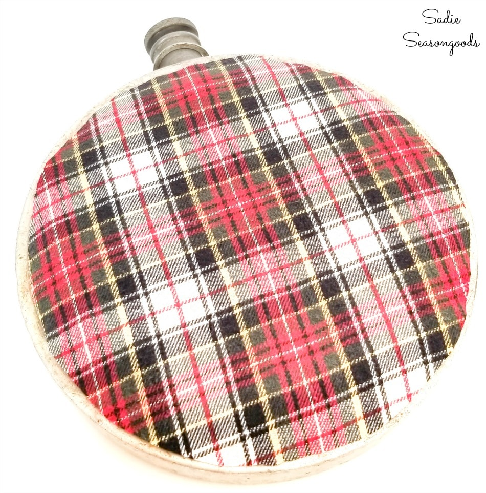 Cutting out the flannel fabric to decoupage on a metal canteen