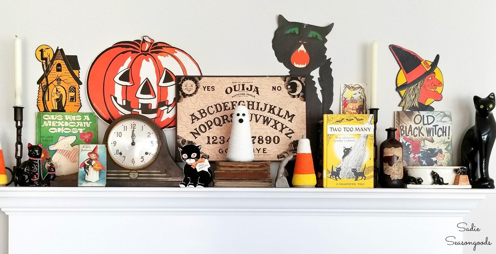 Vintage Halloween cards and door hangers as mantel decor