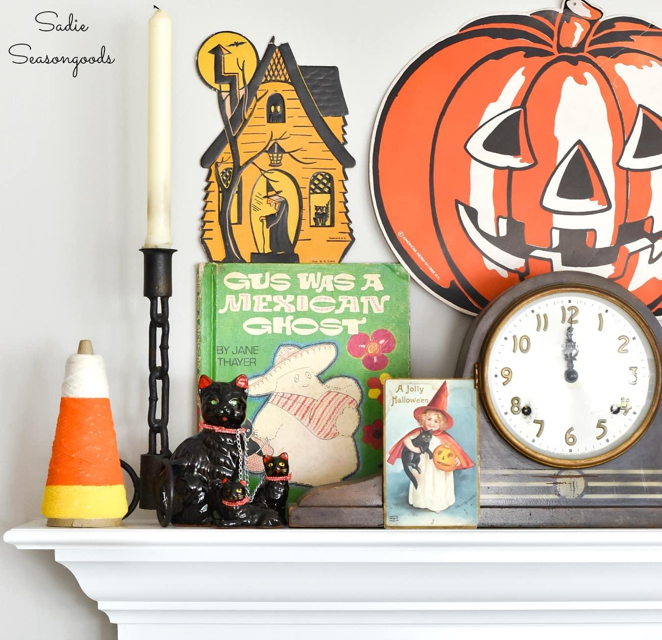 Vintage Halloween post cards and door hangers as mantel decor