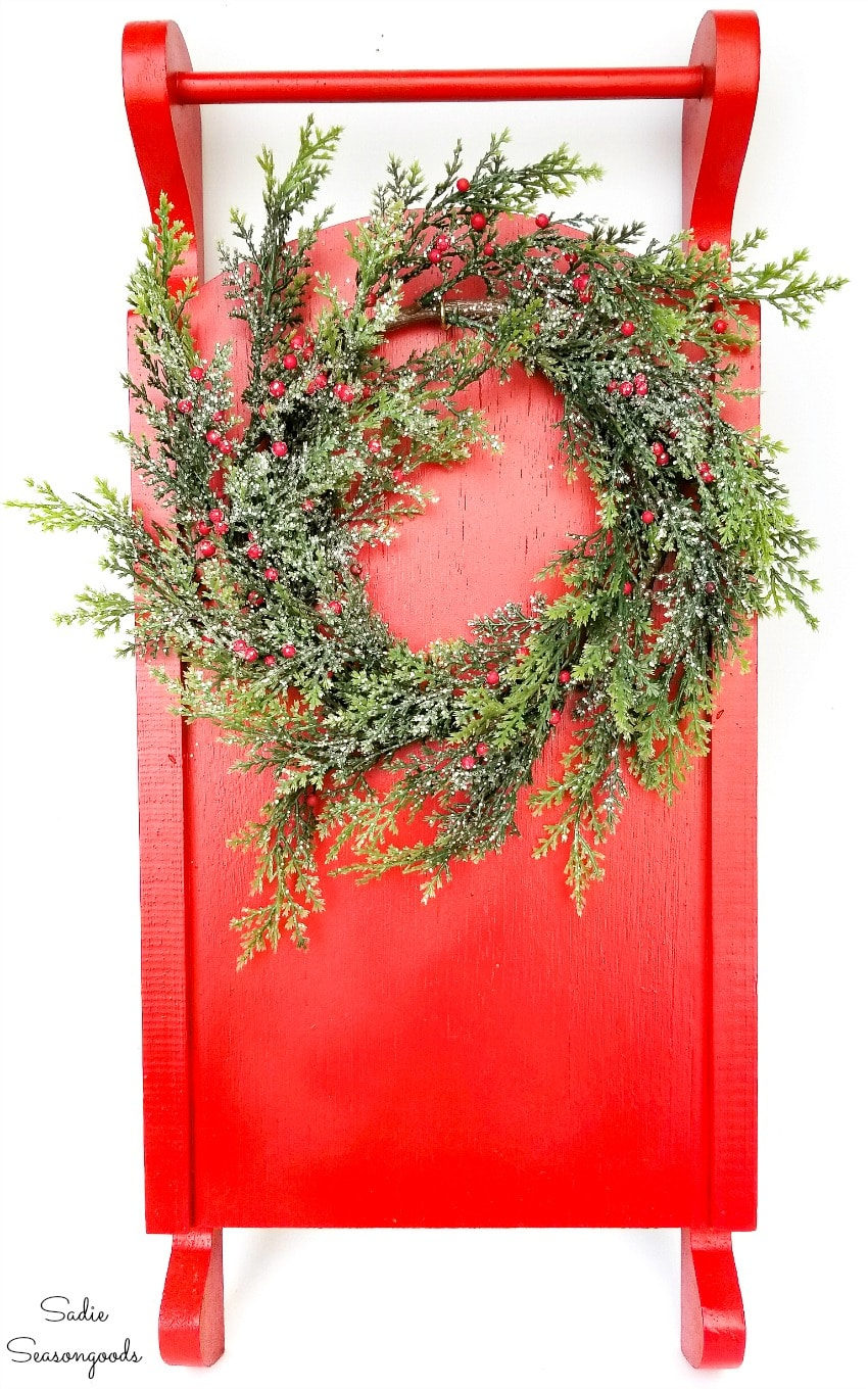 Hanging a wreath on Christmas sled decor